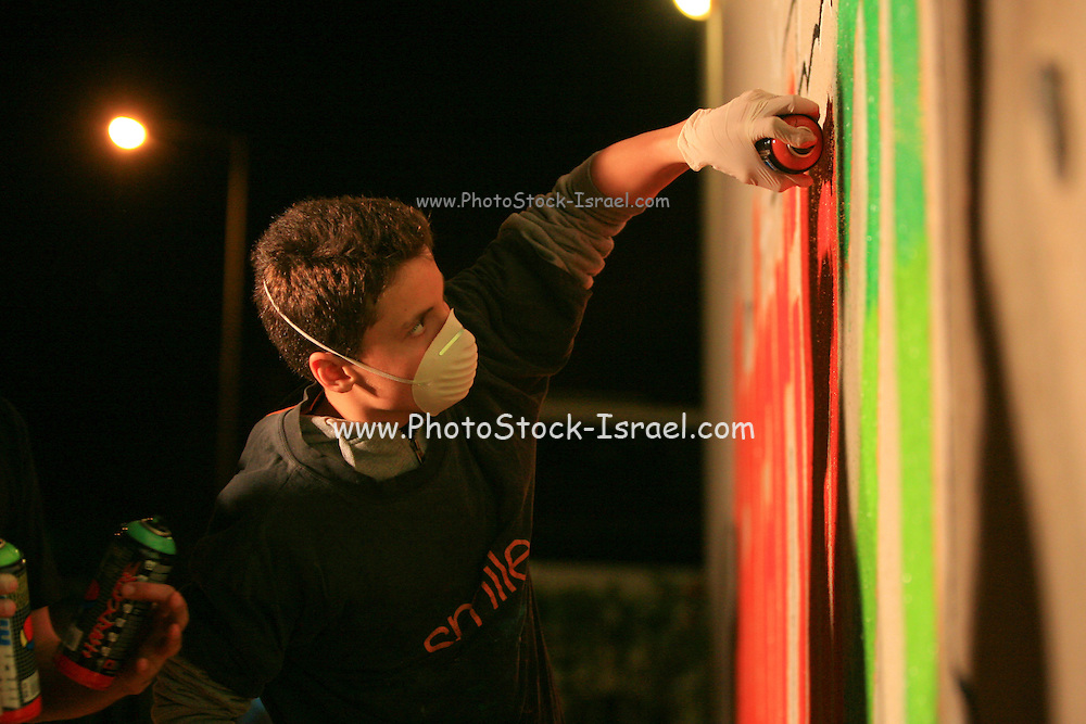 Young teens paint graffiti on a wall