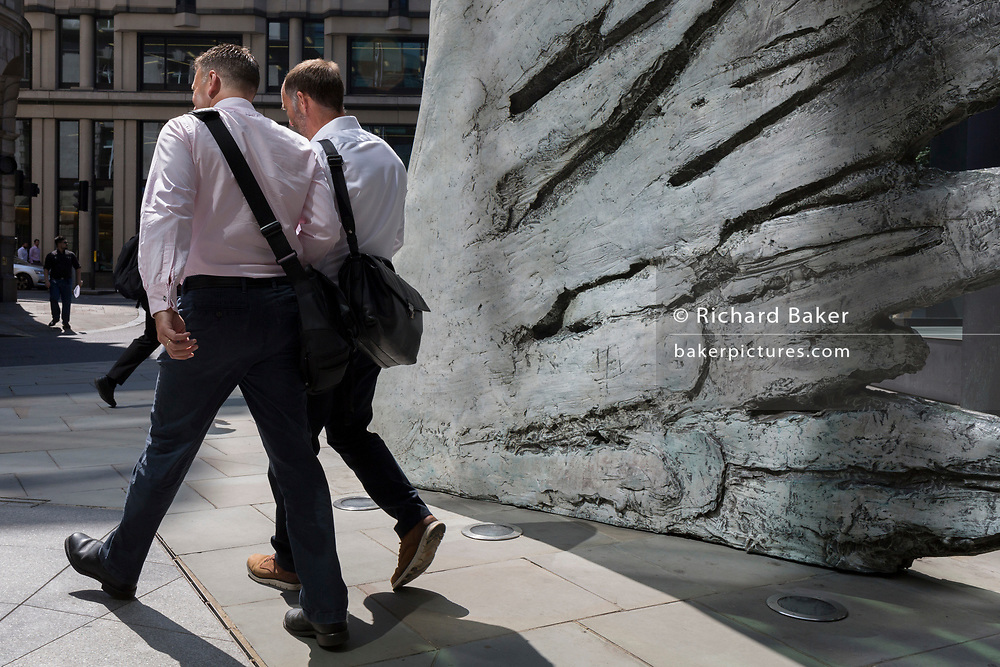 Financial industry businessmen walk past the sculpture entitled City Wing on Threadneedle Street in the City of London, the capital's financial district (aka the Square Mile), on 11th July 2019, in London, England. City Wing is by the artist Christopher Le Brun. The ten-metre-tall bronze sculpture is by President of the Royal Academy of Arts, Christopher Le Brun, commissioned by Hammerson in 2009. It is called 'The City Wing' and has been cast by Morris Singer Art Founders, reputedly the oldest fine art foundry in the world.