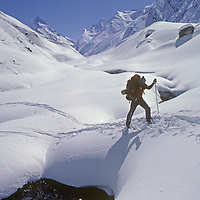 A Ski Mountaineers crosses a stream in the Warwan Valley, en route from Ladakh to Kashmir during an expedition across India's Great Himalaya Range.