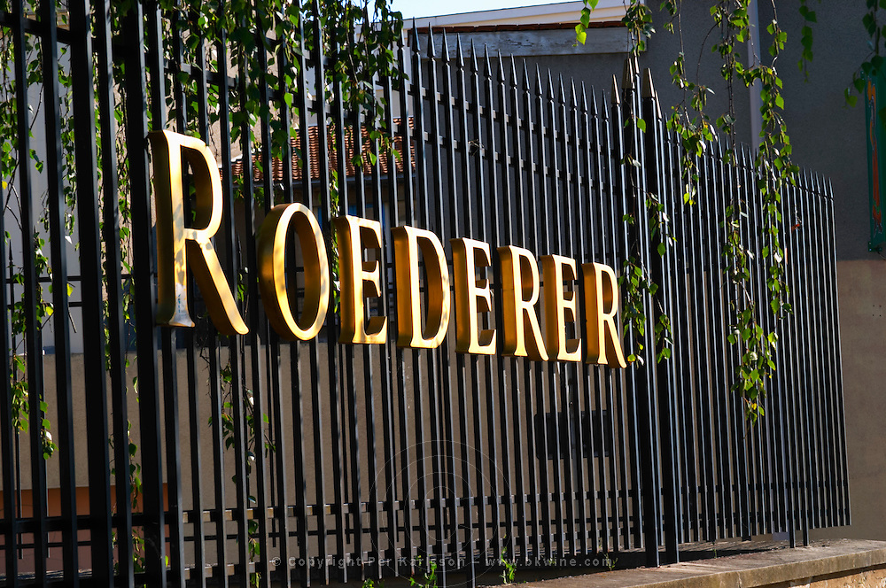 Wrought iron fence with golden letters shining in the setting sun at Champagne Louis Roederer, Reims, Champagne, Marne, Ardennes, France
