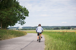 Rear view of a child riding bicycle on road in the countryside, Bavaria, Germany