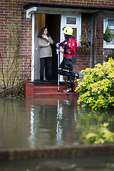 © London News Pictures. 12/02/2014. Egham, UK.  A member of a fire and rescue team talking to a residents of Egham in Surrey whose property is surrounded by flood water. Torrential rain in the area is due to raise water levels increasing the risk of further flooding. Photo credit : Ben Cawthra/LNP