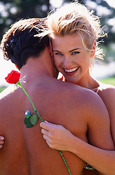blonde girl holding a red rose against a shirtless man's back outdoors