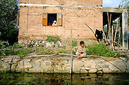 In the back of Dal Lake a young boy passes the time during the strike, by fishing with a flexible branch, while a woman behind him gazes out the window.