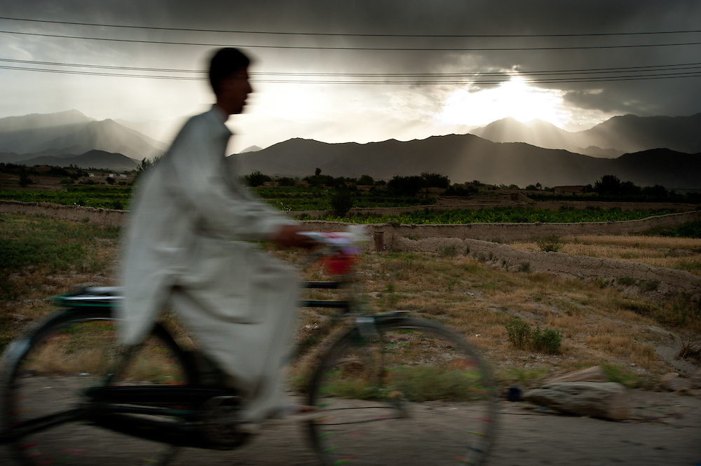 A boy rides his bicycle beside the highway near Bagram, Afghanistan.