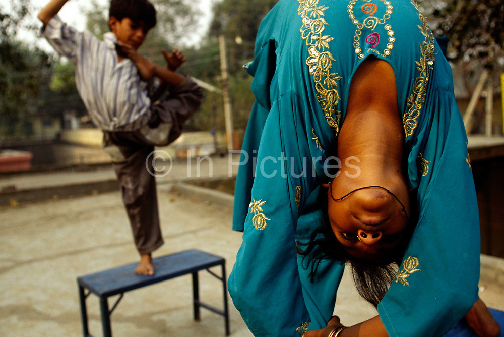 Reenu, 15 and her brother practice their contortions. Reenu and her family are trained by her mother, herself a former acrobat. The children, when babies, were stretched and contorted to make their bones pliable for the act. Shadipur Depot, New Delhi, India<br /> The Kathiputli Colony in the Shadipur Depot slum is home to hundreds of (originally Rajasthani) performers. The artistes who live here - from magicians, acrobats, musicians, dancers and puppeteers are often international renowed by always return to the Shadipur slum.