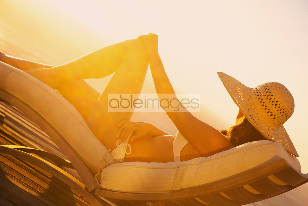 Woman Sunbathing on Recliner Chair at Sunset