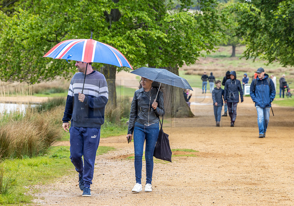 Licensed to London News Pictures. 16/05/2021. London, UK. Members of the public brave the rain in Richmond Park, South West London as they make the most of the bad weather as miserable May continues with grey skies and more rain with temperatures down to 13c. Weather forecasters predict yet more showers for the rest of the weekend and into next week as the bad Spring weather continues. Photo credit: Alex Lentati/LNP