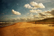Man taking a walk in the morning sun on the beach - photograph edited with texture overlays
