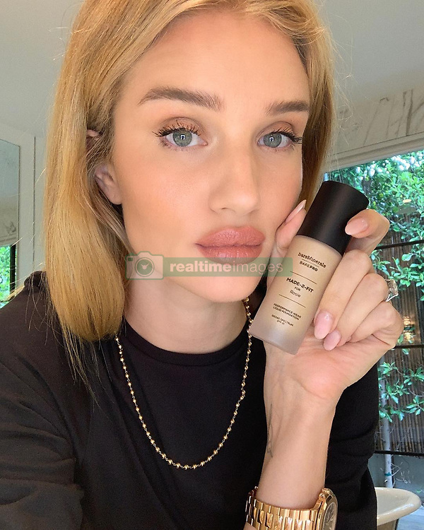 """Rosie Huntington-Whiteley releases a photo on Instagram with the following caption: """"One of my favorite #bareminerals products, BAREPRO Liquid Foundation SPF 15, is now available to customize to your unique skin tone using the @bareminerals #MADE2FIT app! Simply download the app to create a bespoke blend of makeup made fresh\u2014just for you. Plus, the bottle comes with your name on it! #Ad"""". Photo Credit: Instagram *** No USA Distribution *** For Editorial Use Only *** Not to be Published in Books or Photo Books ***  Please note: Fees charged by the agency are for the agency's services only, and do not, nor are they intended to, convey to the user any ownership of Copyright or License in the material. The agency does not claim any ownership including but not limited to Copyright or License in the attached material. By publishing this material you expressly agree to indemnify and to hold the agency and its directors, shareholders and employees harmless from any loss, claims, damages, demands, expenses (including legal fees), or any causes of action or allegation against the agency arising out of or connected in any way with publication of the material."""