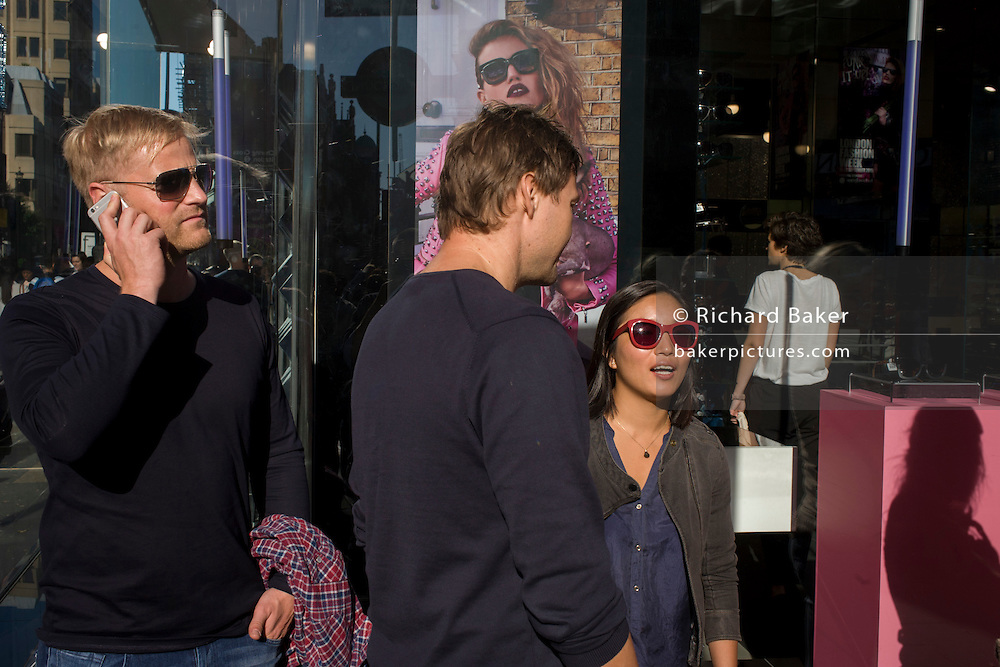 A sunglasses theme with young people in front of a Sunglasses Hut shop in Covent Garden.
