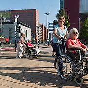 Nederland Rotterdam 28 september 2011 20110928  Straatbeeld  Rotterdam Kop van Zuid, bejaarde dames in rolstoel worden voortgeduuwd door vrijwilligers van stichting zonnebloem. Uitje, kwaliteit van leven, positiviteit, positief zijn blijven, ouderdom komt met gebreken, gezondheidsklachten. Foto: David Rozing