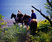 Heather Robbins and Lori Egge riding horses along the shore of Raspberry Strait, Raspberry Island, Kodiak Archipelago, Alaska.