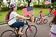 A family rides bicycles decorated with bunting and American flags during the Daniel Island Independence Day parade July 3, 2015 in Charleston, South Carolina.