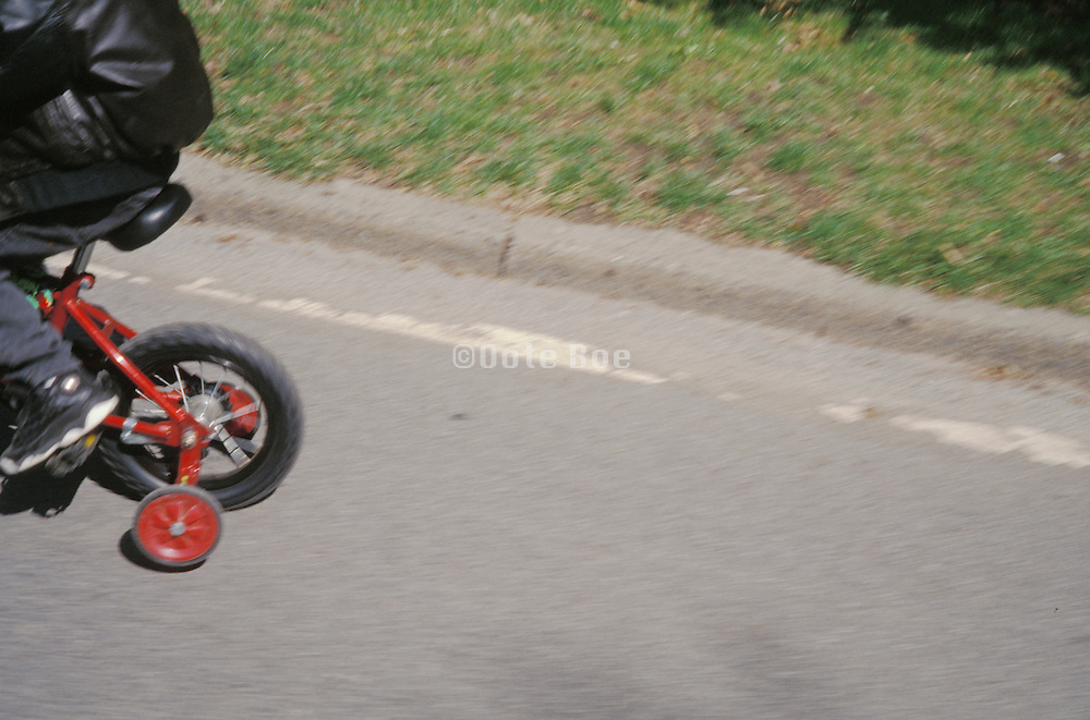 A boy riding away on a bike with red training wheels