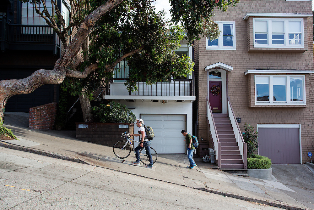 Een fietser loopt de steile heuvel op Lombard Street in San Francisco omhoog. De Amerikaanse stad San Francisco aan de westkust is een van de grootste steden in Amerika en kenmerkt zich door de steile heuvels in de stad. Ondanks de heuvels wordt er steeds meer gefietst in de stad.<br /> <br /> A cyclist walks the steep hill at Lombard Street in San Francisco. The US city of San Francisco on the west coast is one of the largest cities in America and is characterized by the steep hills in the city. Despite the hills more and more people cycle.
