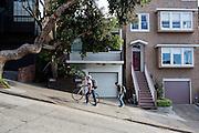 Een fietser loopt de steile heuvel op Lombard Street in San Francisco omhoog. De Amerikaanse stad San Francisco aan de westkust is een van de grootste steden in Amerika en kenmerkt zich door de steile heuvels in de stad. Ondanks de heuvels wordt er steeds meer gefietst in de stad.<br /> <br /> A cyclist walks the steep hill at Lombard Street in San Francisco. The US city of San Francisco on the west coast is one of the largest cities in America and is characterized by the steep hills in the city. Despite the hills more and more people cycle.
