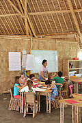 """Primary school class. Class agreements are that they will be respectful, work hard, be safe clean and have fun. Everything is made of bamboo or local plants. The Whiteboards are made from recycled windscreens and shockproof glass painted white on the inside.<br /><br />The Green School (Bali) is one of a kind in Indonesia. It is a private, kindergarten to secondary International school located along the Ayung River near Ubud, Bali, Indonesia. The school buildings are of ecologically-sustainable design made primarily of bamboo, also using local grass and mud walls. There are over 600 students coming from over 40 countries with a percentage of scholarships for local Indonesian students.<br /><br />The impressive three-domed """"Heart of School Building"""" is 60 metres long and uses 2500 bamboo poles. The school also utilizes renewable building materials for some of its other needs, and almost everything, even the desks, chairs, some of the clothes and football goal posts are made of bamboo.<br /><br />The educational focus is on ecological sustainability. Subjects taught include English, mathematics and science, including ecology, the environment and sustainability, as well as the creative arts, global perspectives and environmental management. This educational establishment is unlike other international schools in Indonesia. <br /><br />Renewable energy sources, including solar power and hydroelectric vortex, provide over 50% of the energy needs of the school. The school has an organic permaculture system and prepares students to become stewards of the environment. <br /><br />The school was founded by John and Cynthia Hardy in 2008."""