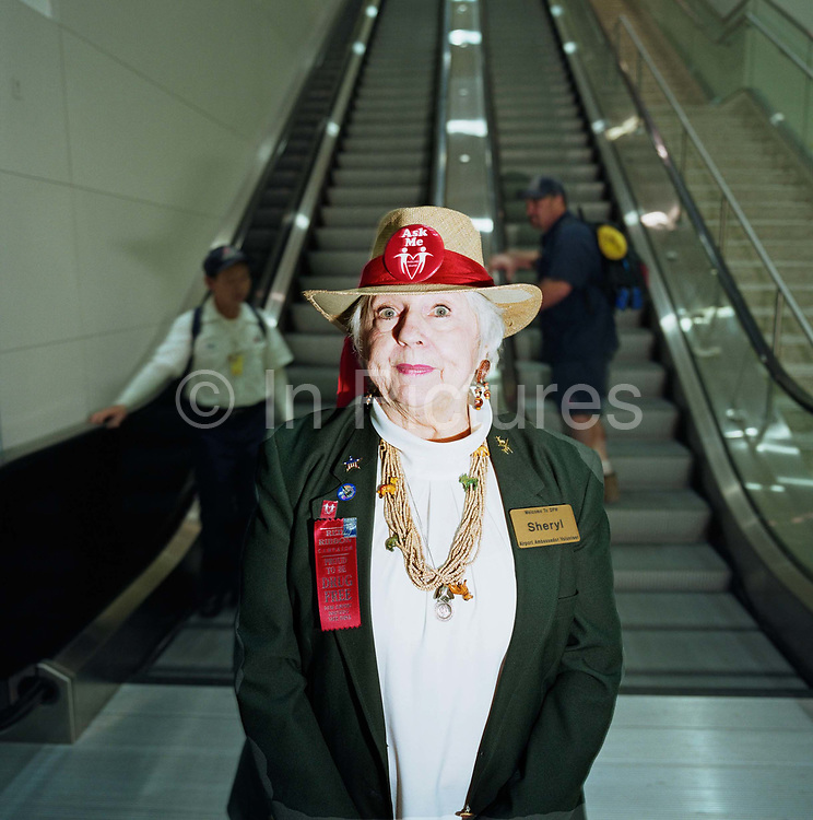 Sheryl is an Airport Ambassador Volunteer at Dallas Fort Worth, Texas and stands for a portrait at the foot of some escalators in the main terminal. She sports a straw hat saying 'Ask Me' in red and a name badge with her job title although she comes to the airport to assist strangers at her city's airport, hoping her good nature and charitable efforts will help uncertain travellers find their way. Also on her jacket is a the phrase 'Proud to be Drug Free .. Airport Narcotics Task Force.' 'Fort Worth is the sixth busiest airport in the world transporting 59,064,360 passengers in 2005. Picture from the 'Plane Pictures' project, a celebration of aviation aesthetics and flying culture, 100 years after the Wright brothers first 12 seconds/120 feet powered flight at Kitty Hawk,1903.