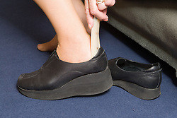 Woman putting on orthopaedic shoe with built up heel to correct different leg lengths caused by curvature of the spine,