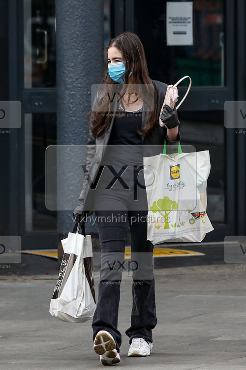 A girl carrying her shopping bags, wearing face protective mask and surgical gloves is seen walking near Tottenham Court Road underground station in central London on Monday, May 11, 2020. <br /> U.K. Prime Minister Boris Johnson fleshed out his plan for lifting the U.K. lockdown in Parliament as he seeks to get more people back to work, even as resistance from politicians and labour unions laid bare the hurdles facing the government as it seeks to kickstart the economy. (Photo/ Vudi Xhymshiti)