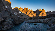 """Sunrise on Pingora Peak seen from Jackass Pass, Cirque of the Towers, Bridger Wilderness, Wind River Range, Bridger-Teton National Forest, Rocky Mountains, Wyoming, USA. We backpacked to Big Sandy Lake Campground (11 miles round trip with 1000 feet gain). Two hours before sunrise, I departed from Big Sandy Lake to reach Jackass Pass viewpoint for Cirque of the Towers and Lonesome Lake (6.5 miles round trip, 1860 ft gain) on the Continental Divide Trail. The Continental Divide follows the crest of the """"Winds"""". Mostly composed of granite batholiths formed deep within the earth over 1 billion years ago, the Wind River Range is one of the oldest mountain ranges in North America. These granite monoliths were uplifted, exposed by erosion, then carved by glaciers 500,000 years ago to form cirques and U-shaped valleys. This image was stitched from multiple overlapping photos."""