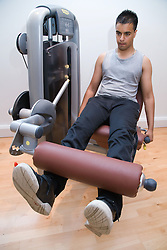 Young man using the leg extension equipment at gym,
