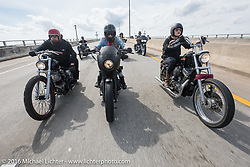 """Jim Root (L) from the Band Slipknot on a Blings Cycles bike alongside Leticia Cline and Kissa Von Addams of the """"Iron Lillies"""" as they cross the Granada Bridge during Daytona Bike Week 75th Anniversary event. FL, USA. Thursday March 3, 2016.  Photography ©2016 Michael Lichter."""
