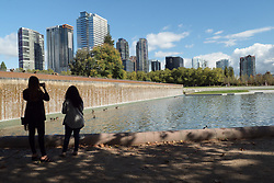 United States, Washington, Bellevue. Pond and waterfall at Downtown Park, with skyline. Editorial Use Only.