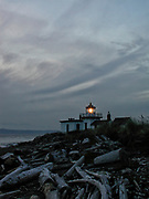 The West Point Light, also known as the Discovery Park Lighthouse, shines above a beach full of driftwood in Discovery Park, Seattle, Washington. West Point Light was the first manned light station on Puget Sound and was activated on November 15, 1881.