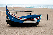 Traditional blue and white wooden Portuguese fishing boat on the beach of Nazare, Portugal. These boats are on display by the Dry Fish Museum