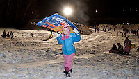 7 year old Haley Burke makes the trek up the hill during Memorial Park's sledding party to try out her vortex sled on Friday evening.  (Karen Bobotas/for the Laconia Daily Sun)