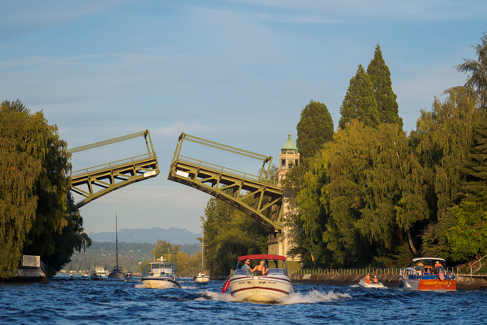 """United States, Washington, Seattle. The Montlake Bridge spans the """"Montlake Cut"""" looking east from Portage Bay to Lake Washington and Cascade Mountains in the distance."""