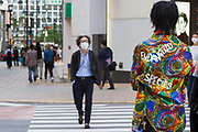 "A man wearing a very colourful shirt with ""Endangered Species"" written on it crosses a quieter than usual street in Shibuya, Tokyo, Japan. Thursday May 7th 2020. The month-long state of emergency declared by the Japanese government in response to the COVID-19 pandemic was due to end on May 7th but was extended to May 31st despite Japan appearing to have avoided the high infection and mortality rates of some countries. Areas like Shibuya have many businesses shuttered and closed and the streets are a lot quieter than usual."
