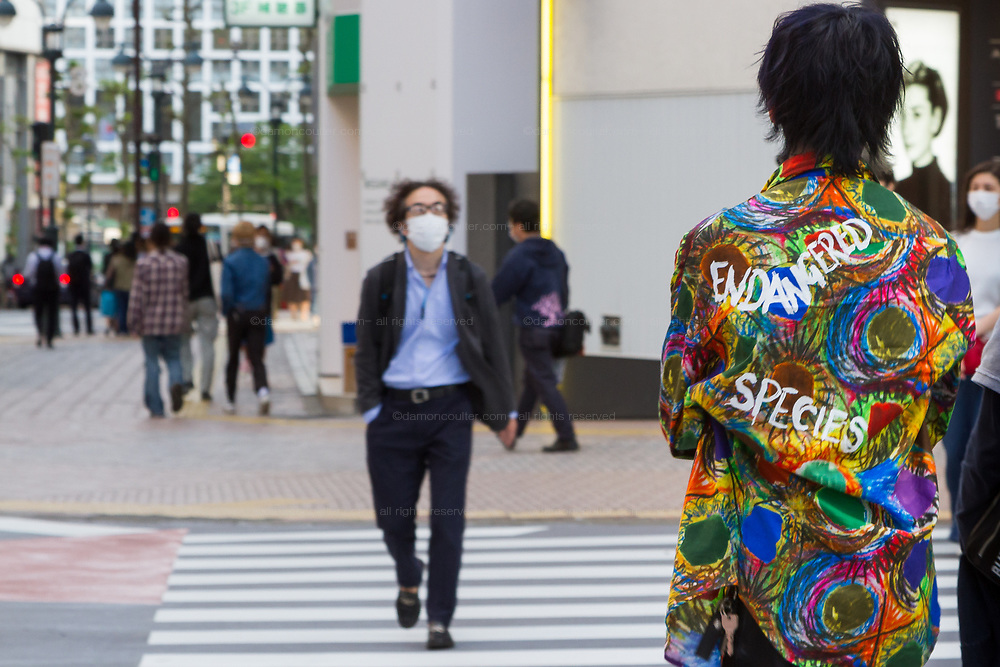 """A man wearing a very colourful shirt with """"Endangered Species"""" written on it crosses a quieter than usual street in Shibuya, Tokyo, Japan. Thursday May 7th 2020. The month-long state of emergency declared by the Japanese government in response to the COVID-19 pandemic was due to end on May 7th but was extended to May 31st despite Japan appearing to have avoided the high infection and mortality rates of some countries. Areas like Shibuya have many businesses shuttered and closed and the streets are a lot quieter than usual."""