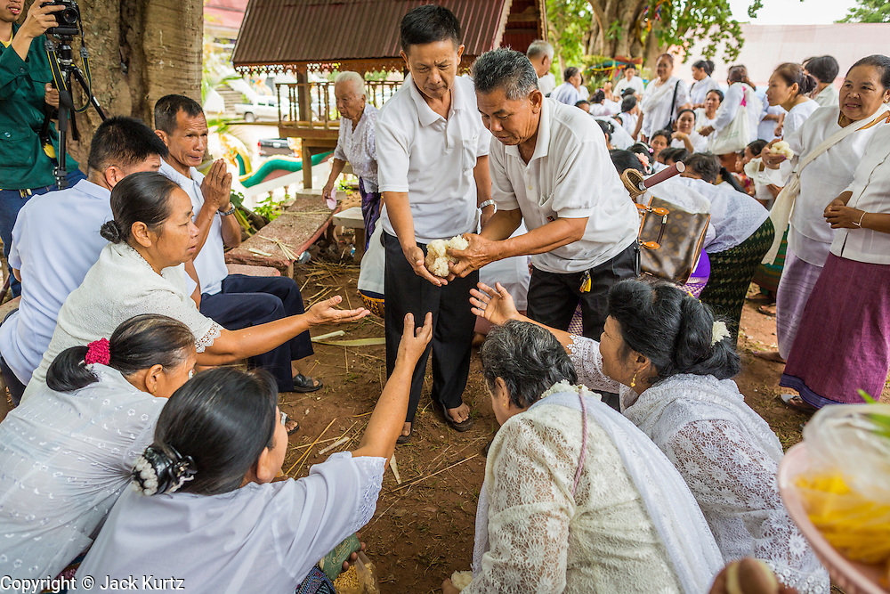 29 JUNE 2014 - DAN SAI, LOEI, THAILAND: People make merti during a ceremony in Wat Ponchai on the last morning of the Ghost Festival. Phi Ta Khon (also spelled Pee Ta Khon) is the Ghost Festival. Over three days, the town's residents invite protection from Phra U-pakut, the spirit that lives in the Mun River, which runs through Dan Sai. People in the town and surrounding villages wear costumes made of patchwork and ornate masks and are thought be ghosts who were awoken from the dead when Vessantra Jataka (one of the Buddhas) came out of the forest. On the last day of the festival people participate in merit making ceremonies at the Wat Ponchai in Dan Sai and lead processions through town soliciting donations for the temple.    PHOTO BY JACK KURTZ