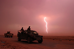 Lightening illuminates the desert and a passing Marine patrol in the wastes outside Najaf, Iraq on Oct. 15, 2004.