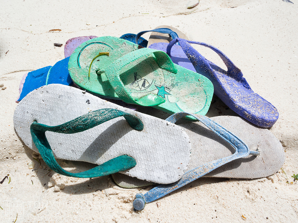 Discarded flip-flops, garbage on a white-sand beach in popular holiday and tourism destination Palau