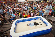 A competitor lays face down in a pool of instant grits during the grits roll competition at the World Grits Festival April 14, 2012 in St. George, SC. The festival celebrates the southern love for the sticky corn porridge
