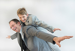 Father giving piggy back ride to his son, smiling