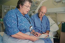 Elderly male patient sitting on hospital bed on ENT ward talking to nurse specialist,