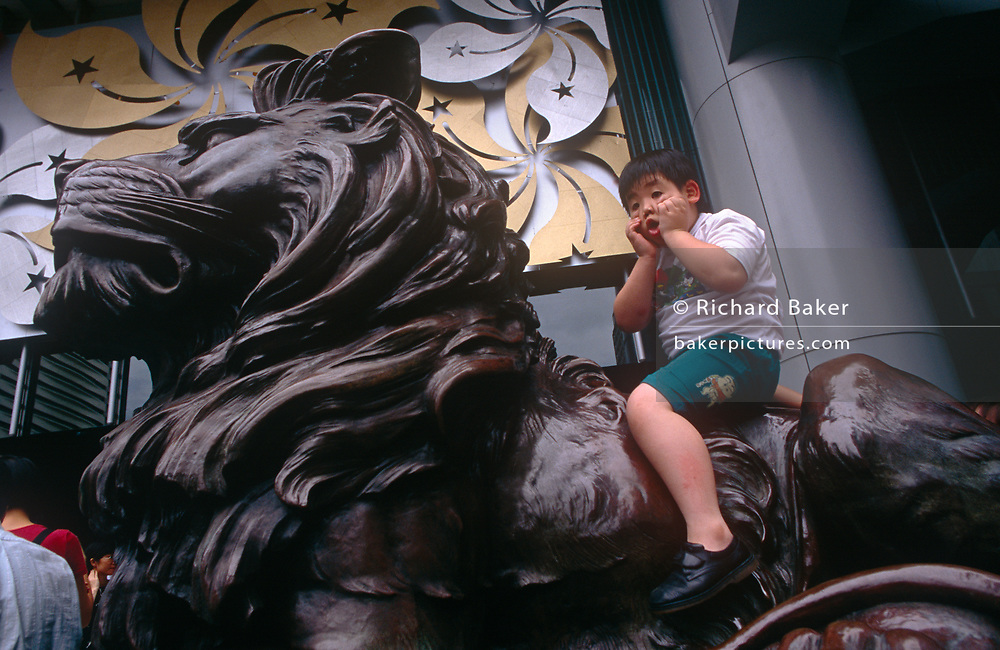 A young Chinese boy pulls a face on top of a lion at the HSBC bank in Central, the day after the Handover of sovereignty from Britain to China, on 30th June 1997, in Hong Kong, China. Midnight signified the end of British rule, and the transfer of legal and financial authority back to China. Hong Kong was once known as 'fragrant harbour' (or Heung Keung) because of the smell of transported sandal wood.
