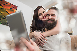 Couple embracing and watching digital tablet