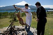 Chef roasting lamb, Lake Llanquihue and Osorno Volcano, Chile..MODEL RELEASED