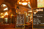 The menu on a chalk black board blackboard chalkboard with Lillet written on it with this month's special offers on wine and a menu with the desserts. A big mirror reflecting the bar and the chandelier The Bistrot du Peintre is an old fashioned Paris café cafe bar restaurant of art nouveau design with polished brass, mirrors and old signs