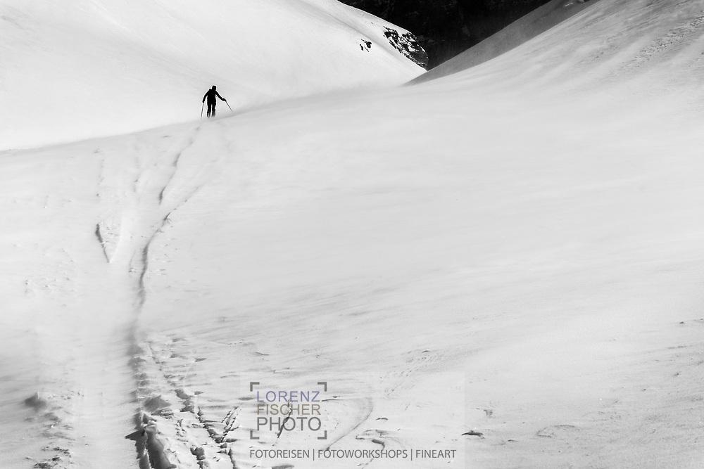 Snow drift and a ski tourer, who is climbing up to mount Glatten, Muotathal, Schwyz, Switzerland