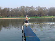 A member of the Serpentine Swimming Club stretches before going swimming in the lake, Hyde Park, London, UK. The Serpentine Lake is situated in Hyde Park, London's largest central open space. The Serpentine Swimming Club was formed in 1864 'to promote the healthful habit of bathing in open water throughout the year'.  Its headquarters were beneath an old elm tree on the south side of the lake, a wooden bench for clothing being the only facility.  At this time London was undergoing rapid expansion and Hyde Park was now in the centre of a densely populated built up area and provided a place of relaxation to its urbanised masses. Now, the club has its own (somewhat spartan) changing facilities and members are  permitted by the Royal Parks to swim in the lake any morning before 09:30.  They race every Saturday morning throughout the year, regardless of the weather.