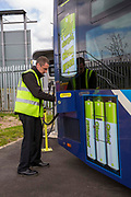 A Nottingham Community Transport bus driver plugging in one of the Ecolink zero emissions buses to charge in Nottingham, Nottinghamshire, United Kingdom.