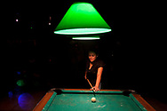 Yesenio Rodriguez shoots pool as her co-workers and house mates dance to live music at a local bar.