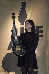 A staff member holds a guitar once owned by Prince on display ahead of the the Entertainment Memorabilia Sale at Bonhams in Knightsbridge, London later this week.